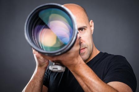 若い、写真撮影中に彼のスタジオでプロの男性カメラマン (トーン色イメージ; 浅い自由度)
