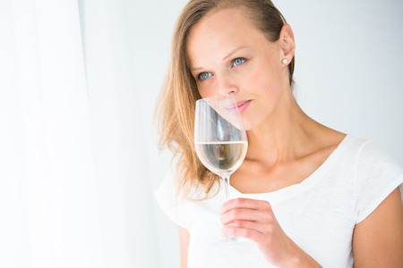 sip: Gorgeous young woman with a glass of wine, smelling the lovely drink, savouring every sip (shallow DOF; color toned image)