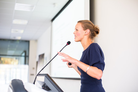 Pretty, young business woman giving a presentation in a conference/meeting setting