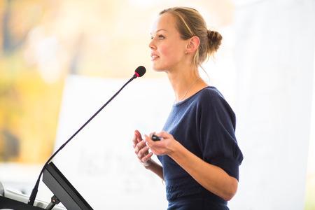 Mooie, jonge zakenvrouw het geven van een presentatie in een conferentie  instelling vergadering