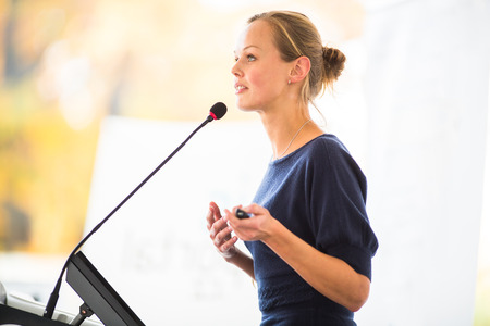 auditorium: Pretty, young business woman giving a presentation in a conferencemeeting setting