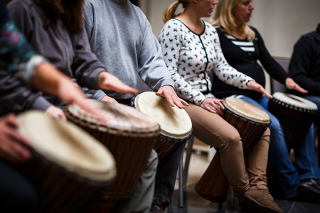 music: Group of people playing on drums - therapy by music Stock Photo