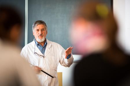 profesor: Profesor de química mayor que da una conferencia en frente de aula llena de estudiantes