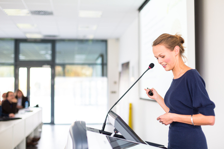 talk: Pretty, young business woman giving a presentation in a conferencemeeting setting
