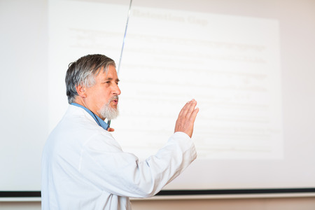 lecturing hall: Senior chemistry professor giving a lecture in front of classroom full of students