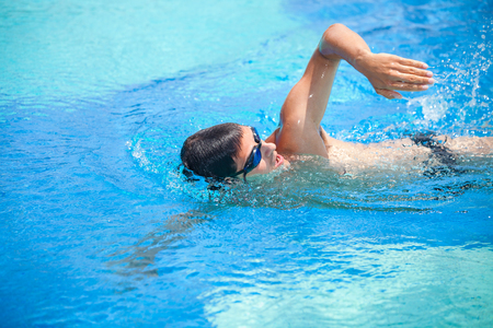 arm: Young man swimming the front crawl in a pool