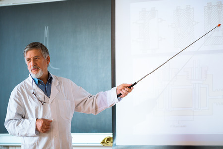 Senior chemistry professor giving a lecture in front of classroom full of students