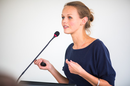 lecture: Pretty, young business woman giving a presentation in a conferencemeeting setting