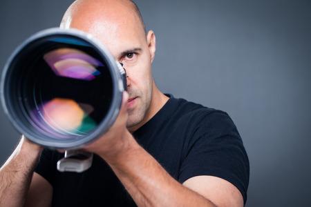 Jonge, professionele mannelijke fotograaf in zijn studio tijdens een fotoshoot