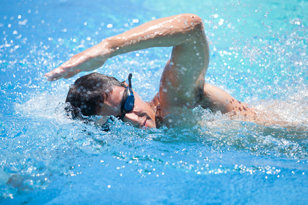 swimming goggles: Young man swimming the front crawl in a pool