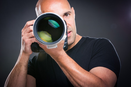 man front view: Young, pro male photographer in his studio during a photo shoot