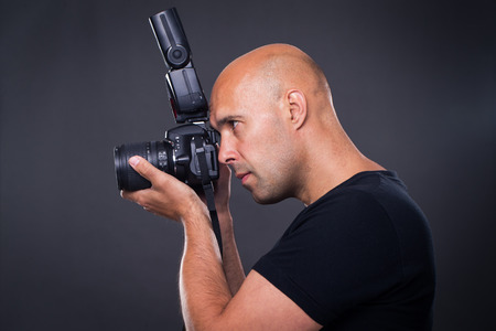pro: Young, pro male photographer in his studio during a photo shoot
