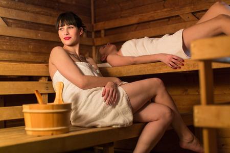 sauna nackt: Junge Frau liegt entspannt in der Sauna