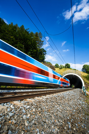railroads: Fast train passing through a tunnel on a lovely summer day (motion blurred image) Stock Photo