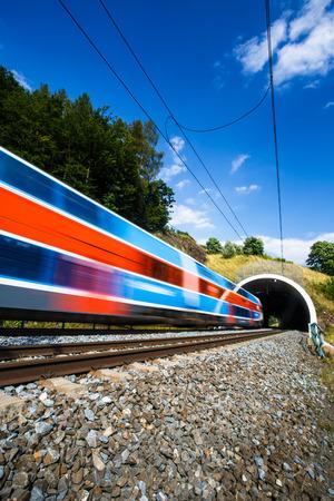 ferrocarril: Tren rápido que pasa a través de un túnel en un hermoso día de verano (movimiento de la imagen borrosa) Foto de archivo
