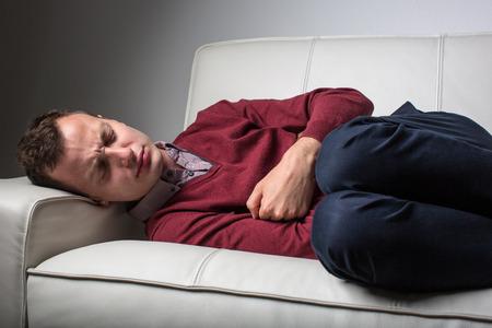 persona triste: Enfermedad hombre joven que sufre de dolor de panza severo, siendo acorralado por la condici�n debilitante de la enfermedad cel�aca  de Crohn