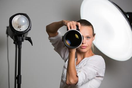 Fotógrafo bonito, femenino con cámara digital - DSLR y un teleobjetivo enorme (imagen a color entonado, DOF bajo)