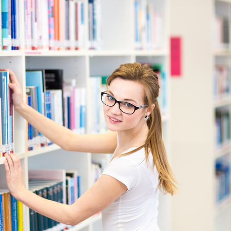 library book: Pretty, female college student in a library, looking for a book (shallow DOF; color toned image) Stock Photo