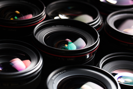 camera lens: Modern camera lenses with reflections, low key image