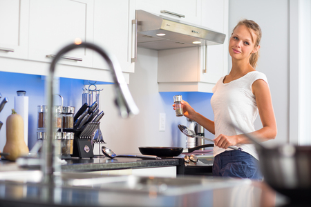 energy efficient: Pretty, young woman in her modern, clean and bright kitchen, fixing lunch (color toned imagey; shallow DOF)