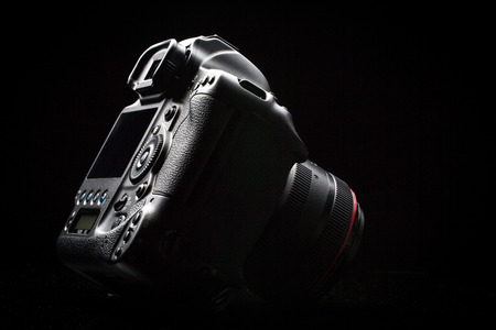 eos: Professional modern DSLR camera low key image - Modern DSLR camera with a very wide aperture lens on