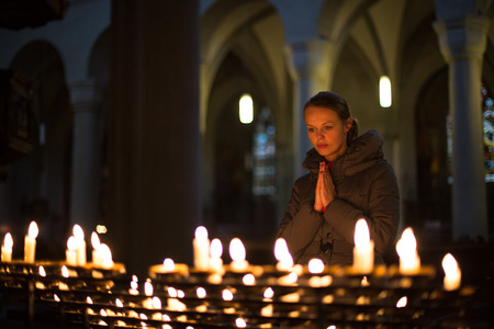 personal god: Young woman praying in a church