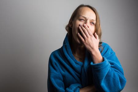 Slaperige jonge vrouw met wijd open mond geeuw