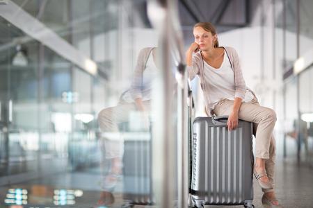 Jonge vrouwelijke passagier bij de luchthaven, wachtend op haar vertraagde vlucht