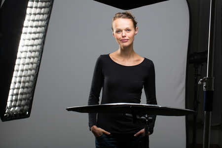 strobe: Beautiful female model posing in a photographic studio surrounded by professional strobe lights