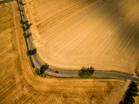 aerial view: Aerial view of a country road amid fields with a red car Stock Photo