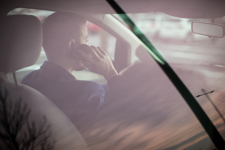 road safety: Handsome young man calling on his cellphone while at the wheel of his car