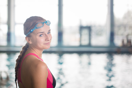 wet suit: Female swimmer in an indoor swimming pool - going for her swim (shallow DOF) Stock Photo