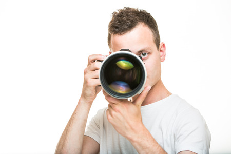 sexy photo: Young pro photographer with digital camera - DSLR and a huge telephoto lens in his well equiped studio, taking photos (color toned image; shallow DOF)