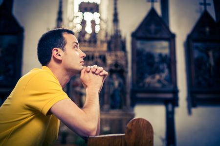 Beau jeune homme en prière dans une église Banque d'images