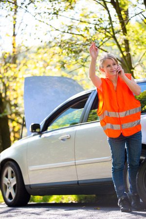 warning vest: Young female driver wearing a high visibility vest, calling the roadside serviceassistance after her car has broken down Stock Photo