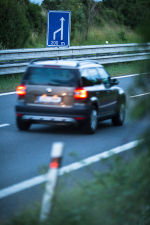convey: Blurred car on a highway (motion blur technique used to convey movement) Stock Photo