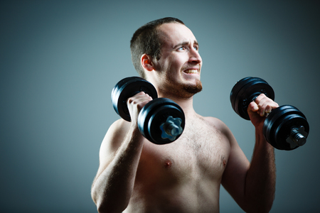 powerful man: Close up of young man lifting weights over grey background