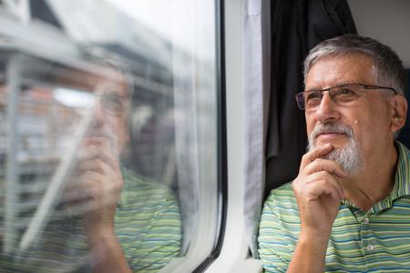 Senior homme appréciant un train Voyage - laissant sa voiture à la maison, il savoure le temps de déplacement, regarde par la fenêtre, a le temps d'admirer le paysage en passant