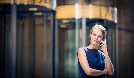 hablando por telefono: Bonita, joven empresaria hablando por teléfono delante de un moderno edificio en Manhattan (DOF, imagen en color entonado)