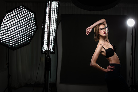 strobe lights: Beautiful female model posing in a photographic studio surrounded by professional strobe lights