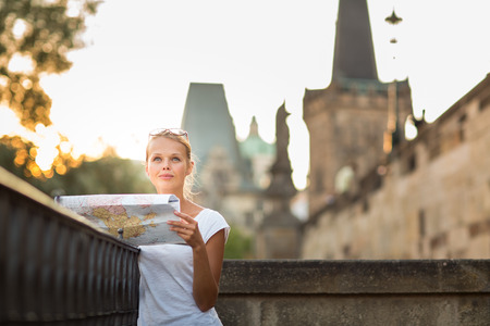 lost city: Pretty young female tourist studying a map, enjoying discovering a new city, looking excited (shallow DOF; color toned image) Stock Photo