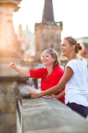 old women: Mother and daughter traveling - two female tourists studying a map, discovering a new city Stock Photo