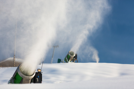 slopes: Snow-machine bursting artificial snow  over a skiing slope to alow for the skiing season to start
