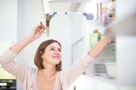 spotless: Young woman in her lovely, modern kitchen