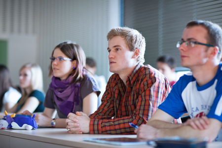 adult classroom: Handsome college student sitting in a classroom full of students during class  (color toned image; shallow DOF) Stock Photo