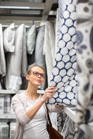 furnishings: Pretty, young woman choosing the right sheets for her bed in a modern home furnishings store (color toned image; shallow DOF)