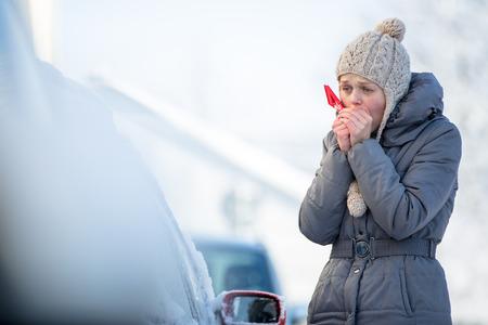 Jeune femme de ménage de sa voiture de la neige et du givre sur un matin d'hiver, elle est glaciale et doit se rendre au travail