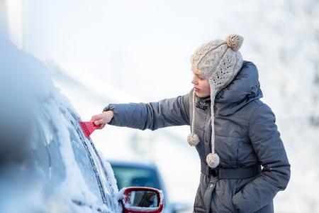 Jonge vrouw het schoonmaken van haar auto uit sneeuw en vorst op een winterse ochtend, wordt ze bevriezen en moet aan de slag