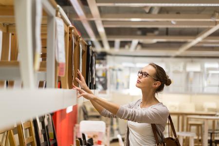 現代の家庭用家具店で彼女のアパートのための右の家具を選択するなり、若い女性 (トーン色イメージ; 浅い自由度)