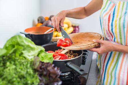 Jonge vrouw koken in haar moderne keuken (ondiepe DOF, kleur getinte afbeelding)